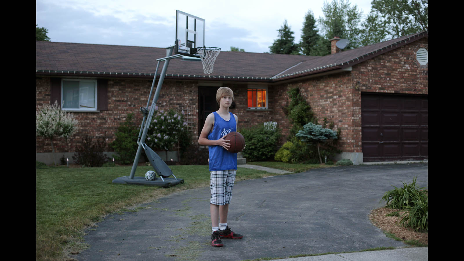 Denver in the driveway where he practices basketball. This is his first year on the basketball team.