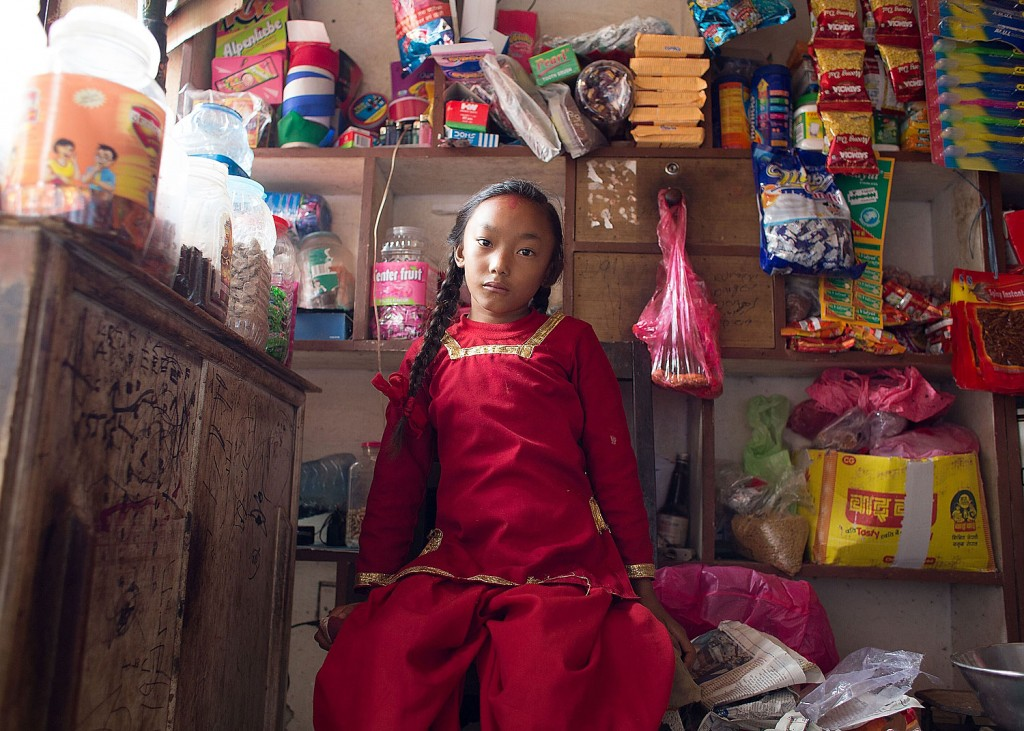 Dangol Kumari sits at the shop run by her family downstairs from their apartment.