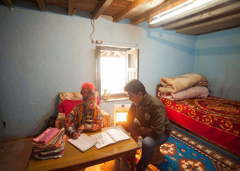 Kumari Samita Bajracharya is home schooled by a tutor. Here, her bedroom doubles as the classroom. Normally she would be dressed in her regular clothing but on this day she did not have time to change.